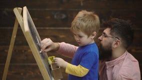 De vader en de zoon schilderden met krijt op een raad Zijaanzicht van weinig jongen en vader die met krijtjes beeld trekken stock videobeelden