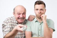 De vader en de zoon selecteren een film om op TV te kijken stock foto's
