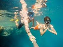 De vader en de zoon snorkelen in ondiep water op koraalvissen stock fotografie