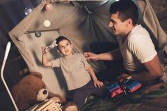 De vader en de zoon spelen thuis met stuk speelgoed vliegtuig en auto's bij nacht stock fotografie