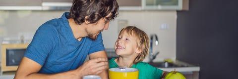 De vader en de zoon spreken en glimlachen terwijl het hebben van een ontbijt in keukenbanner, LANG FORMAAT stock foto's
