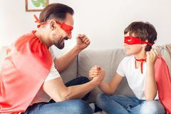 De vader en de zoon in superheroekostuums die thuis op de handen zitten die van de bankholding elkaar bekijken wekten teamgeest o stock foto's