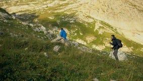 De vader en de zoon van het wandelaarpaar in mooi landschap Van het wandelaarsmens en kind trekking die met rugzakken in sleep in stock footage