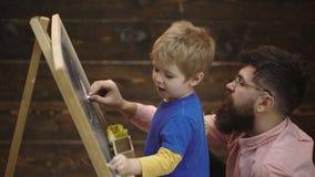 De vader en de zoon zijn geschilderd met krijt op een raad De gelukkige vader onderwijst zijn zoon om op houten achtergrond te tr stock footage