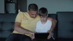 De vader en de zoon zitten op de bank het letten op films en de speelspelen op de tablet Een gelukkige familie stock videobeelden