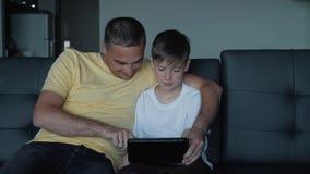De vader en de zoon zitten op de bank het letten op films en de speelspelen op de tablet Een gelukkige familie stock video