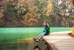 De vader en de zoon zitten op houten brug over het meer Royalty-vrije Stock Foto