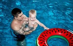 De vader en de zoon zwemmen in de pool stock foto