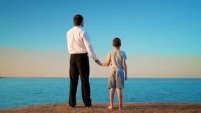 De vader en zoonstribune, door de hand, op de kust, vader richt zijn vinger in de afstand stock videobeelden