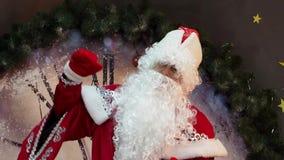 De vader Frost Santa Claus verheugt zich dichtbij reusachtige uren stock videobeelden