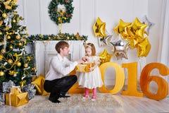 De vader geeft zijn dochter een gift De vooravond 2016 van het nieuwe jaar Royalty-vrije Stock Foto's