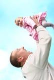 De vader heft zijn babymeisje op Stock Fotografie