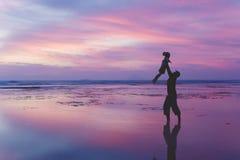 De vader heft zijn dochter op het strand bij schemer op royalty-vrije stock afbeeldingen