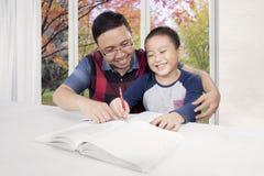 De vader helpt zijn zoon te leren Stock Foto