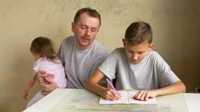 De vader helpt zoon met weg thuiswerk, kleine dochterlooppas stock video