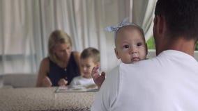 De vader houdt babydochter, bekijkt het meisje camera stock video