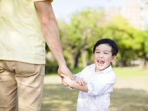 De vader houdt de hand van weinig jongen stock afbeelding