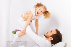 De vader houdt met wapens zijn lachende dochter Royalty-vrije Stock Foto's