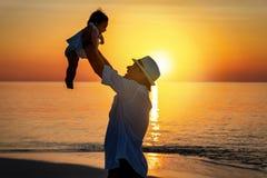 De vader houdt zijn baby in de lucht op een strand tegen royalty-vrije stock afbeelding