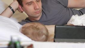 De vader leest het nieuws op de tablet dichtbij de slaapbaby Een jongen die in de voorgrond van een huis op een bed rusten stock footage
