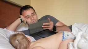 De vader leest het nieuws op de tablet dichtbij de slaapbaby Een jongen die in de voorgrond van een huis op een bed rusten stock video