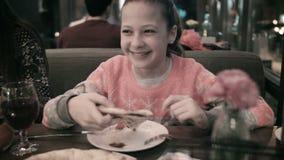 De vader legt een stuk van pizza aan zijn dochter op een plaat voor Een mooi meisje die pizza eten bij een restaurant stock footage