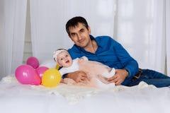 De vader ligt op het bed die zijn kleine dochter koesteren en haar houden door een uiterst kleine voet De baby lacht gelukkig en  stock afbeelding