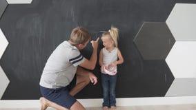 De vader meet de groei van een kleine dochter stock video