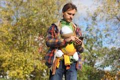De vader met baby in kleurrijke slinger draait aantal op mobiele telefoon Royalty-vrije Stock Afbeelding