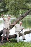De vader met de zoon bij de visserij, toont de grootte van vissen Stock Foto's