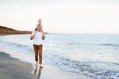 De vader met een blonde zoon op haar schouders loopt langs de kust De vakantie van de familie stock foto