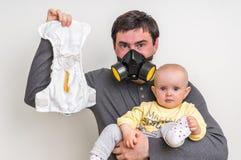 De vader met gasmasker houdt stinky luier en weinig baby Royalty-vrije Stock Foto