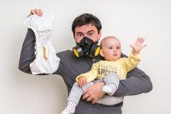De vader met gasmasker houdt stinky luier en weinig baby Royalty-vrije Stock Fotografie