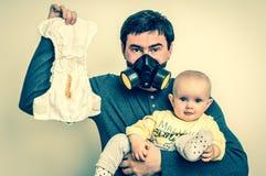 De vader met gasmasker houdt vuile luier en weinig baby Royalty-vrije Stock Foto's