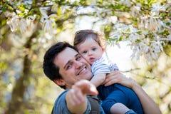 De vader met kind heeft een vrije tijds bloeiende tuin Stock Afbeelding