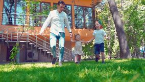 De vader met zijn zoon en weinig dochter die langs de groene grasholding lopen overhandigt dichtbij het huis stock videobeelden
