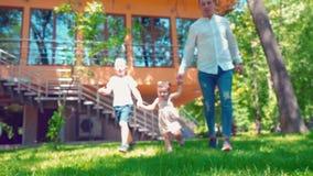 De vader met zijn zoon en weinig dochter die langs de groene grasholding lopen overhandigt dichtbij het huis stock footage