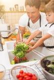 De vader met zoon wast groenten alvorens te eten Royalty-vrije Stock Foto