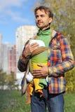 De vader met zuigelingsbaby in slinger houdt de baby met zijn handen Royalty-vrije Stock Afbeelding