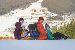 De vader, de moeder en twee kinderen zitten en glimlachen op de achtergrond van de skitoevlucht De winter zonnige dag royalty-vrije stock foto's