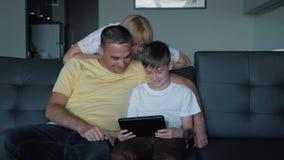 De vader, de moeder en de zoon zitten op de bank het letten op films en de speelspelen op de tablet Een gelukkige familie stock video
