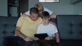 De vader, de moeder en de zoon zitten op de bank het letten op films en de speelspelen op de tablet Een gelukkige familie stock videobeelden