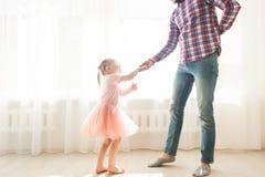 De vader onderwijst om te dansen zijn leuke kleine dochter stock foto's