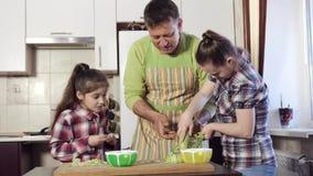 De vader onderwijst zijn dochter, die met Benedensyndroom hoe te om de courgette op een rasp behoorlijk te wrijven stock video