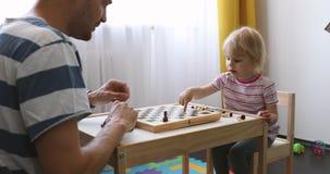 De vader onderwijst zijn kind om schaak thuis te spelen stock video