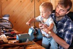 De vader onderwijst zijn peuterzoon om hulpmiddelenbankschroef te gebruiken en in een workshop te raspen Leuke jongen die nieuw m royalty-vrije stock foto