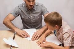 De vader onderwijst zijn zoon om document vliegtuigen te doen Royalty-vrije Stock Fotografie