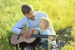 De vader onderwijst zijn zoon om gitaar te spelen Het glimlachen en het bekijken ea Stock Afbeeldingen