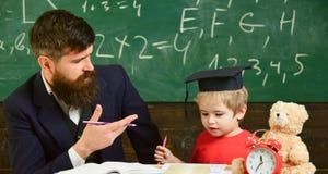De vader onderwijst zoon, bespreekt, verklaart Het concept van het onderwijs Jong geitje die met leraar bestuderen Elementair ond stock foto's