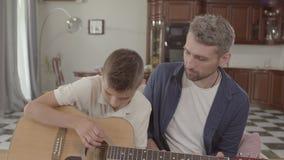 De vader onderwijst zoon om gitaar thuis te spelen De Opvoeding van de familievrije tijd Verhoudingsvader en zoon stock footage